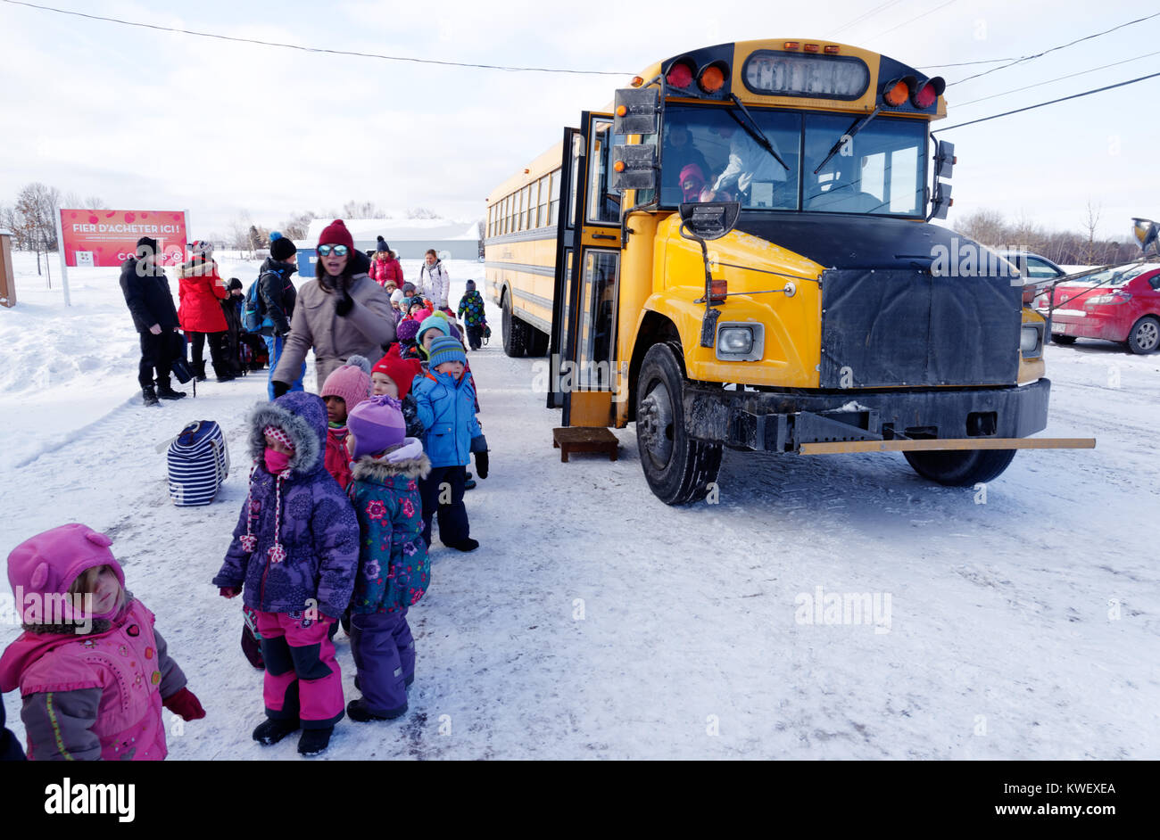A queue of young school children by a school bus in winter in Quebec - Stock Image