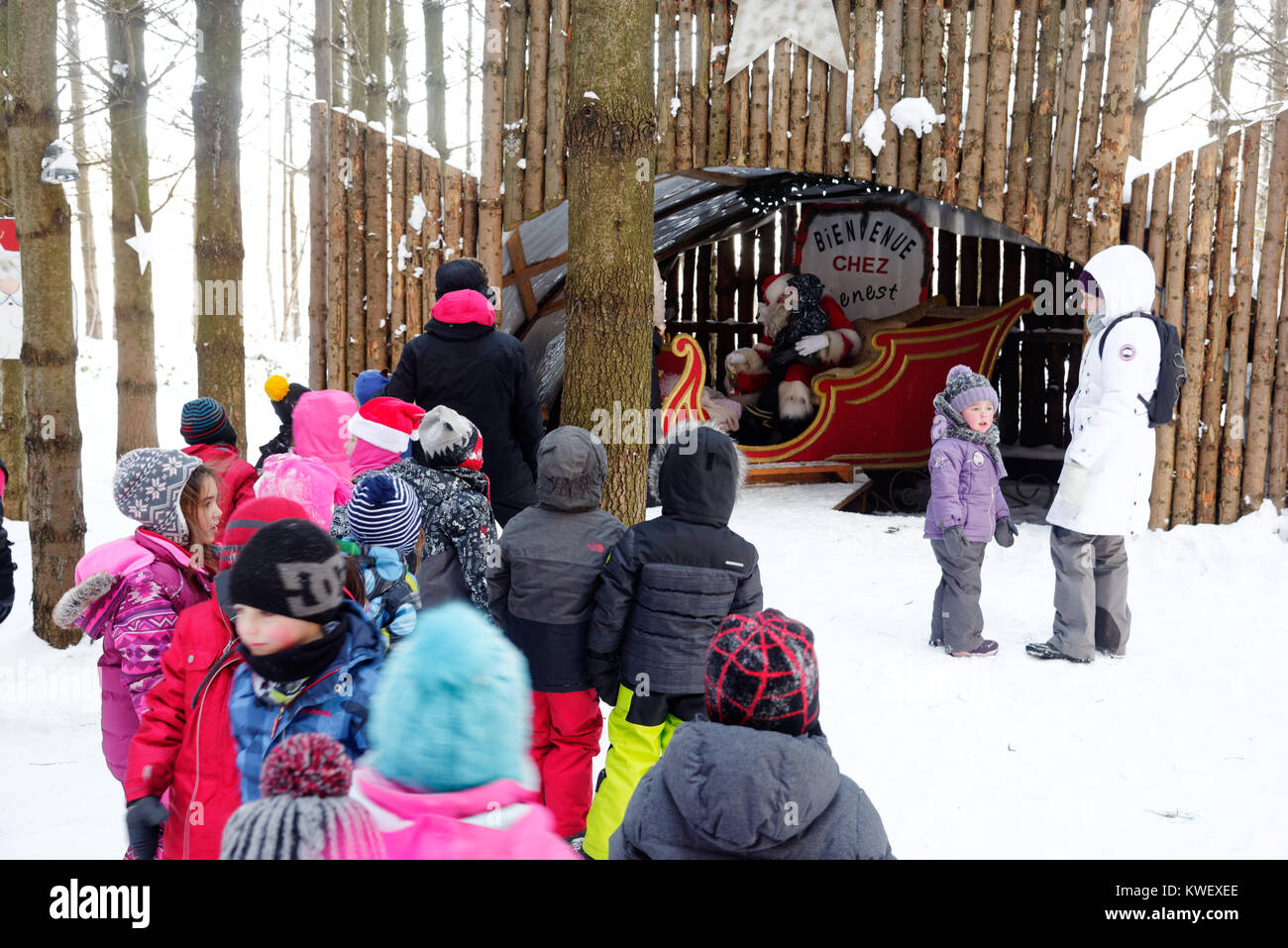 A queue of children waiting in a forest to see father christmas on a achool visit in Quebec. It was -24C. - Stock Image