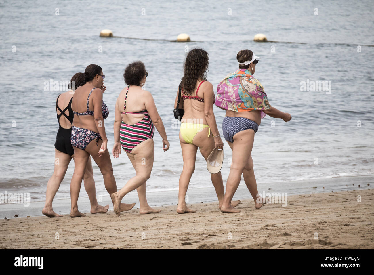 Local Spanish women in swimming costumes walking on beach in Spain - Stock Image