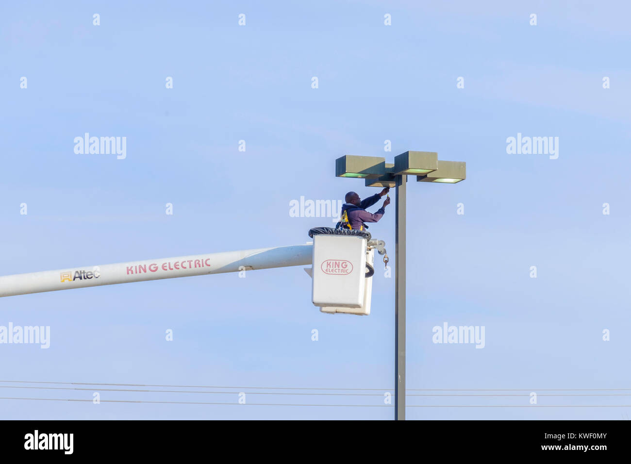 A workman in a lift bucket works on a shopping mall light fixture. Oklahoma City, Oklahoma, USA. - Stock Image