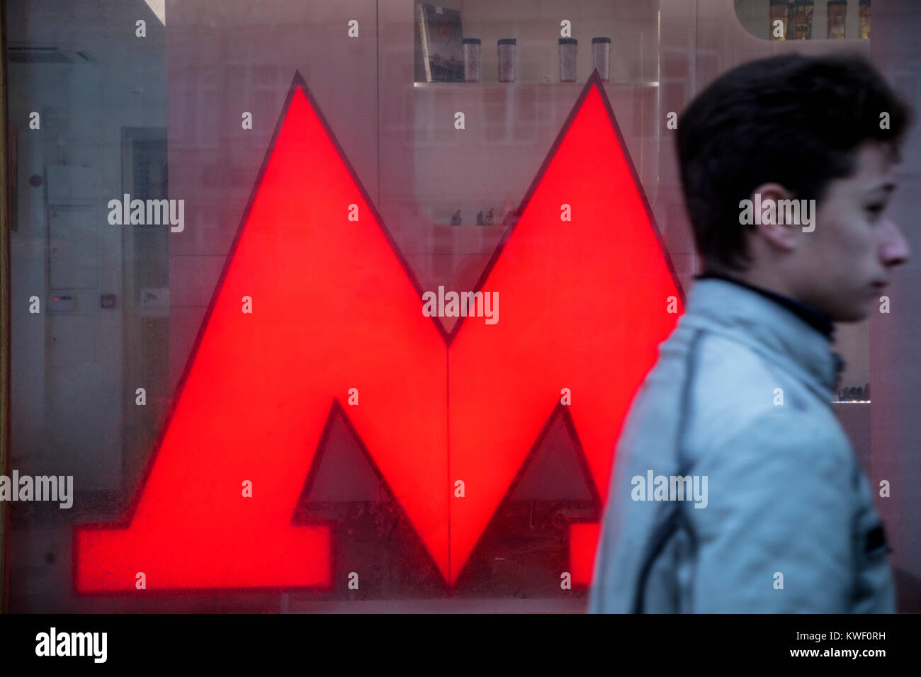 A man goes by the symbol of Moscow subway the letter 'M on central Moscow street, Russia - Stock Image