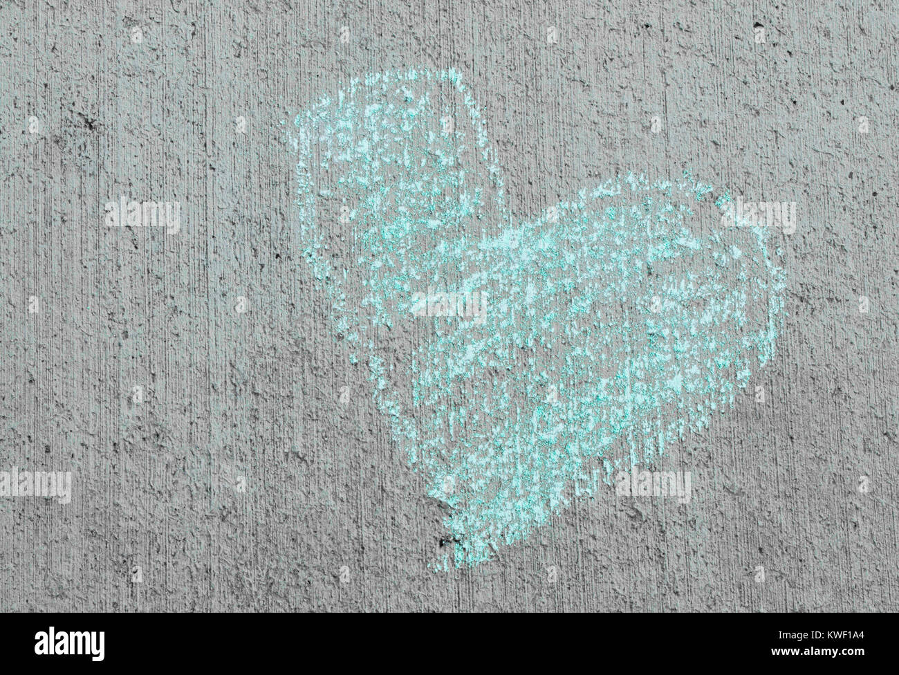 chalk drawing of a turquoise heart on a cement sidewalk - Stock Image
