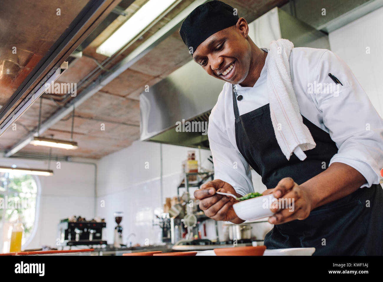Gourmet chef in uniform cooking in a commercial kitchen. Happy male cook wearing apron standing by kitchen counter - Stock Image