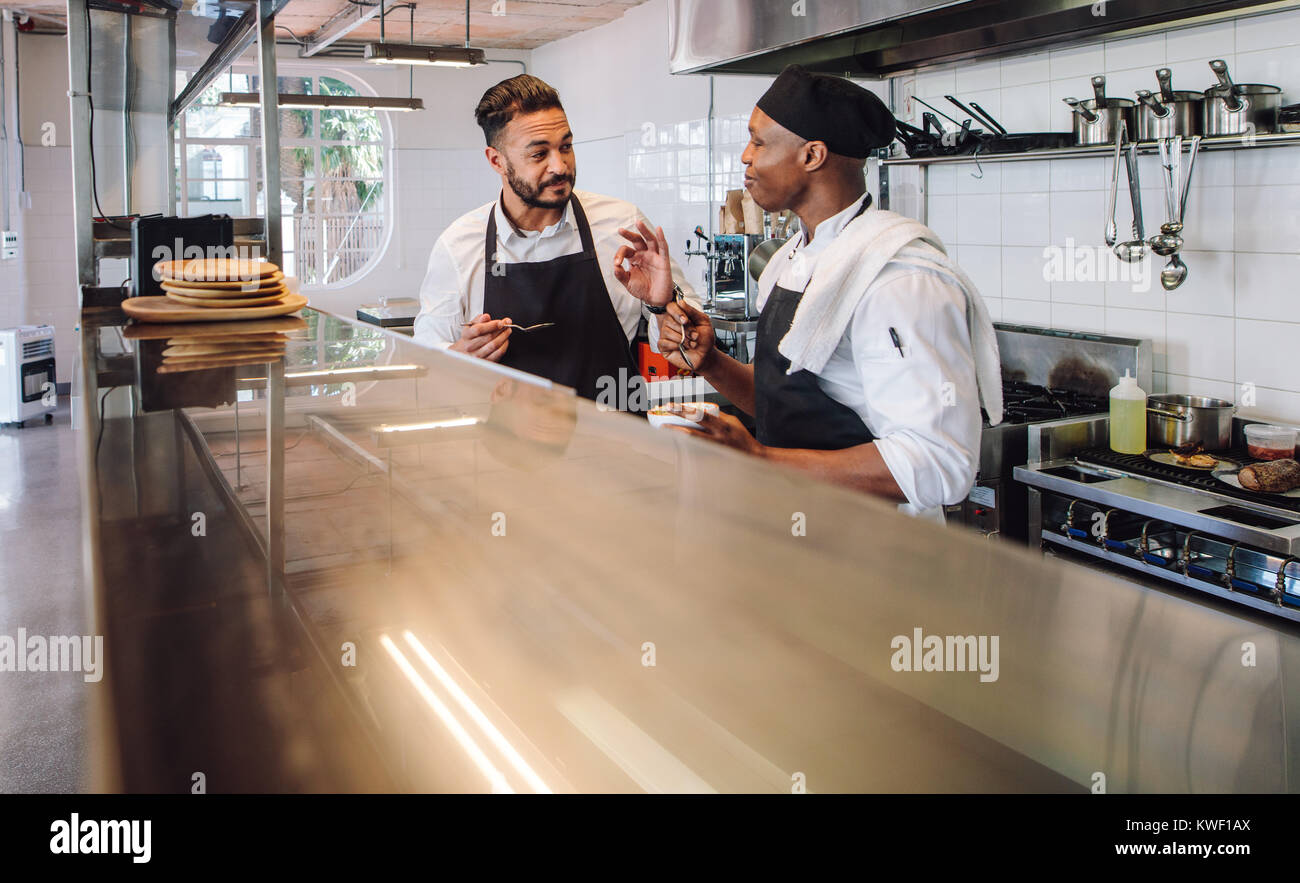 Two male cooks wearing uniform working in commercial kitchen. Professional chefs discussing the taste of new dish - Stock Image