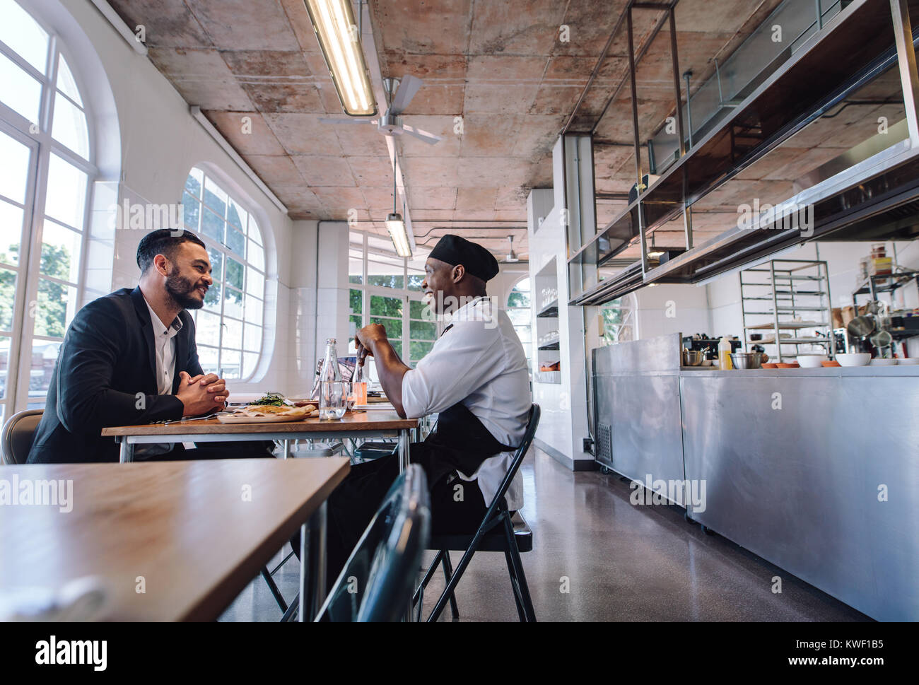 Restaurant manager talking with a professional chef. Cafe owner and cook sitting at a table and talking. - Stock Image