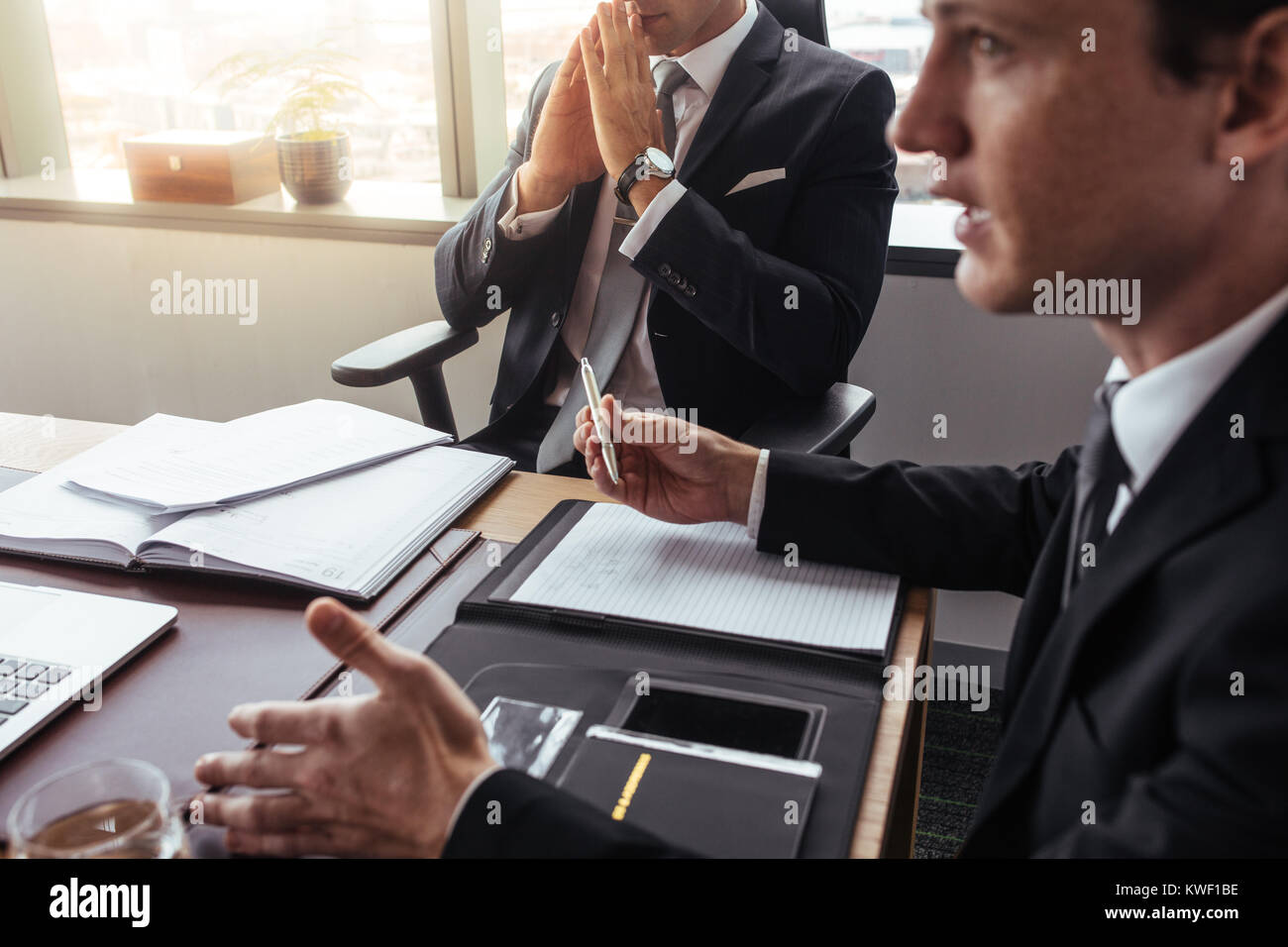 Businessman talking with someone during meeting in office. Two corporate professionals having a meeting together. - Stock Image