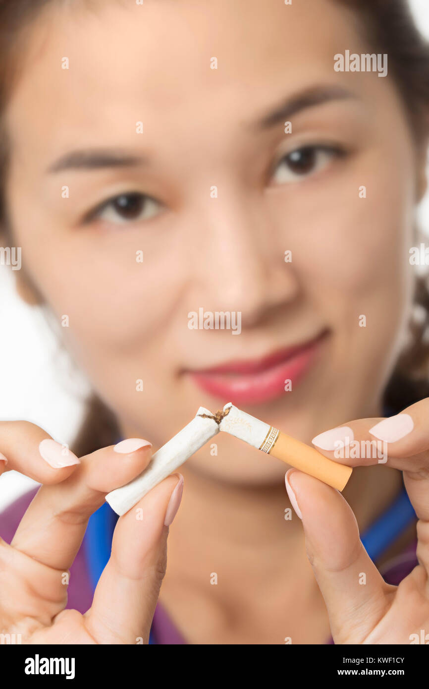 Asian doctor or nurse holding a broken cigarette to illuminate the concept of Quit Smoking isolated on a white background - Stock Image