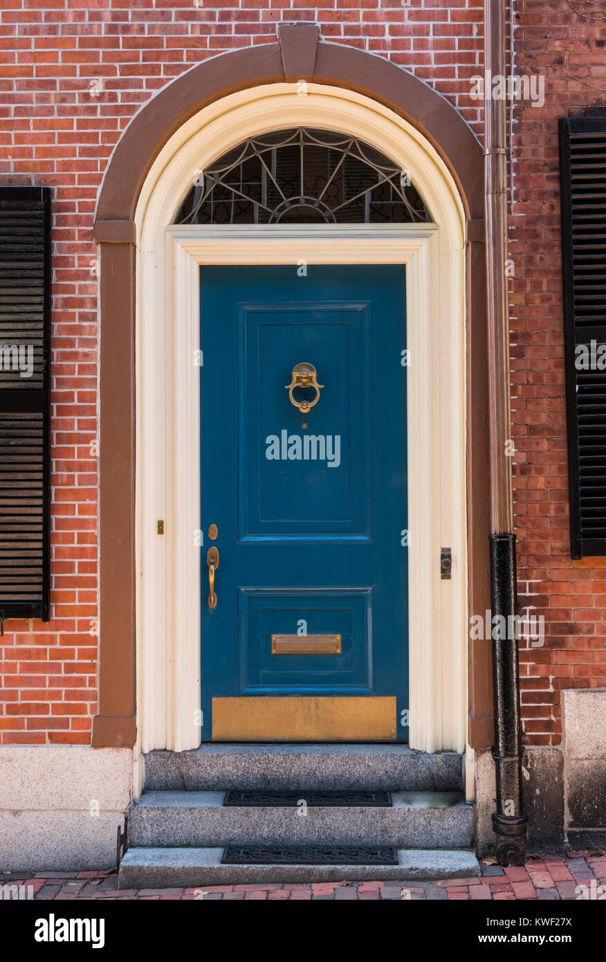 Blue Colonial Door In Arched Frame On Brick Building Stock Photo