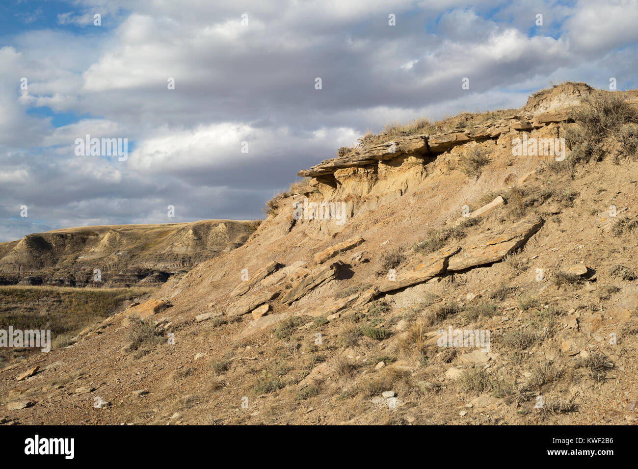 Eroded slopes in Alberta badlands, with sandstone layer above bentonite clay - Stock Image