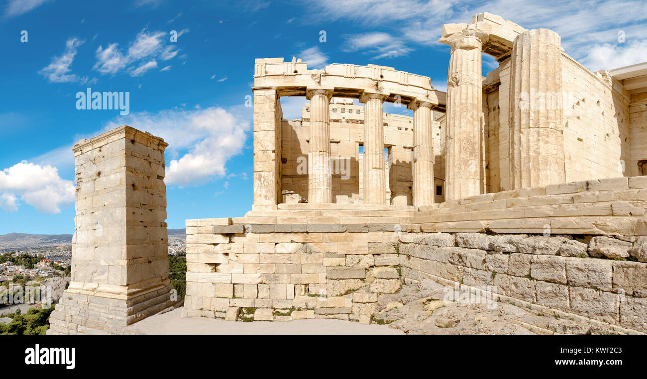 Ruins of an ancient gateway Propylaea in Acropolis fortress, Athens, Greece. Panorama village on a bright day Stock Photo