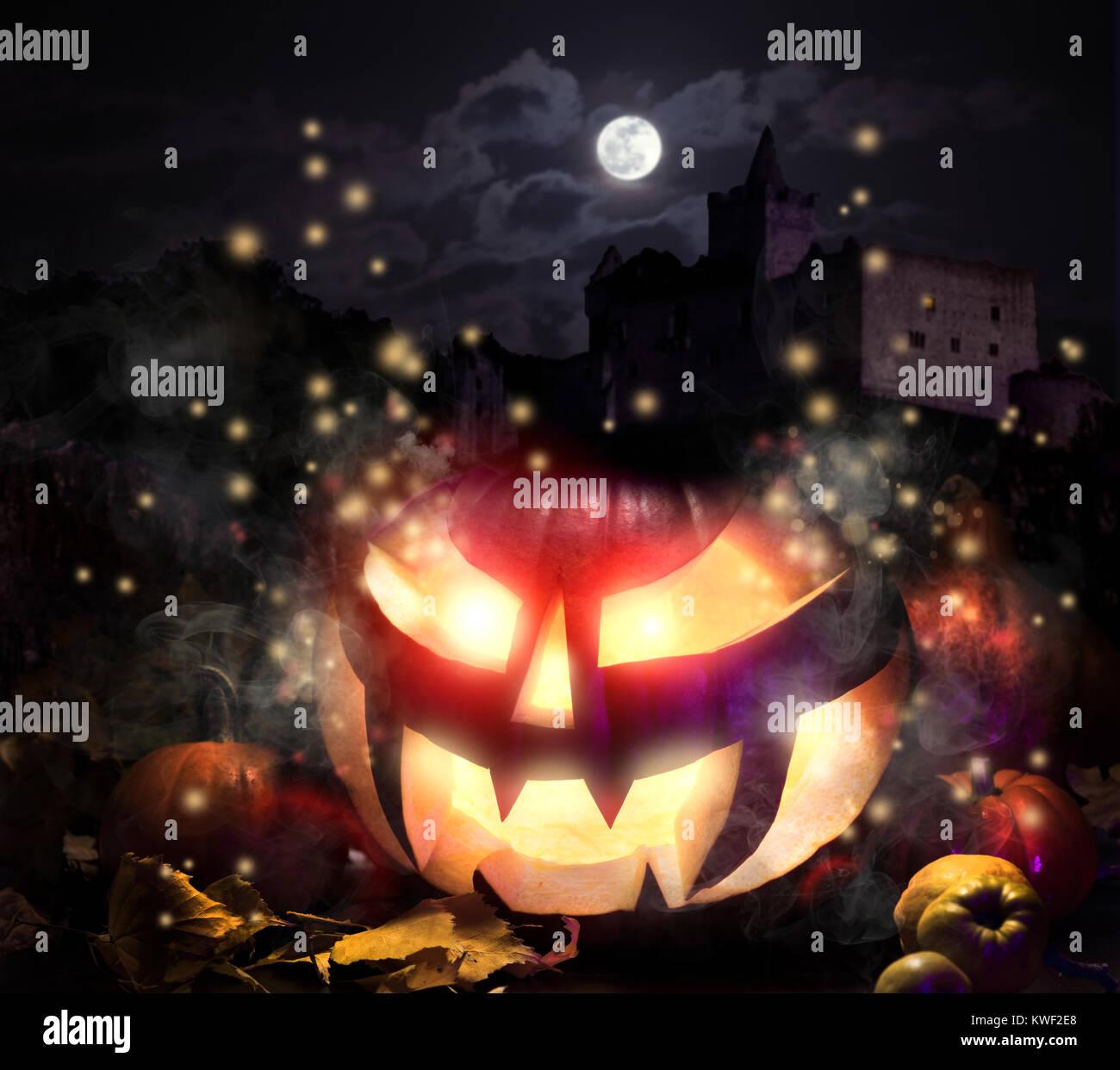 Halloween pumpkin with haunted castle under moonlight - Stock Image