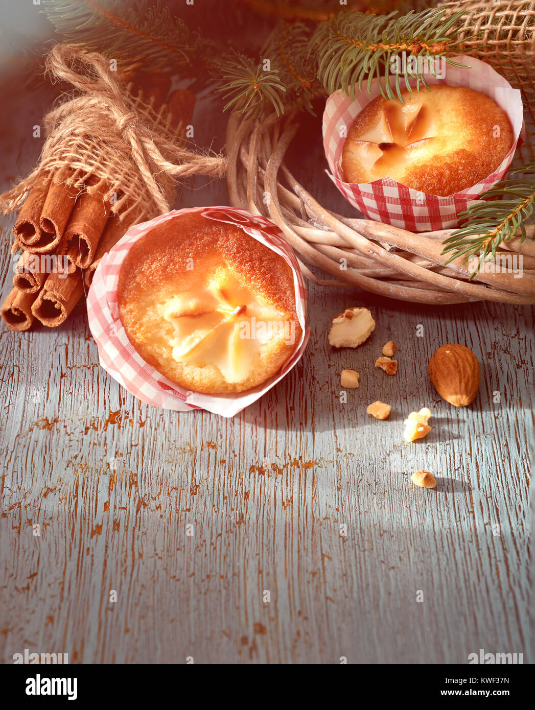 Lemon mini muffins with floral decoration in red-white paper on rustic wooden table with Christmas twigs, almonds - Stock Image