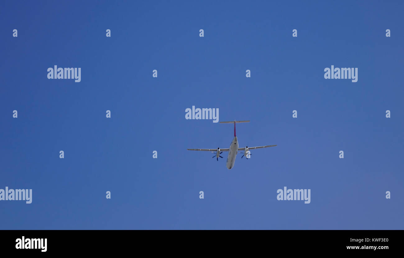 A civil aircraft flying in the blue sky. - Stock Image