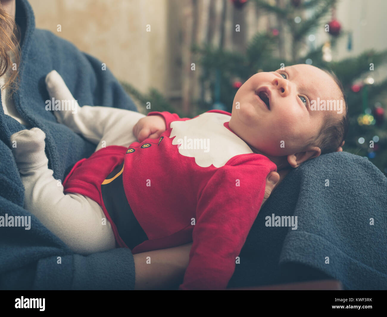 A happy baby wearing a santa outfit in front of the Christmas tree - Stock Image