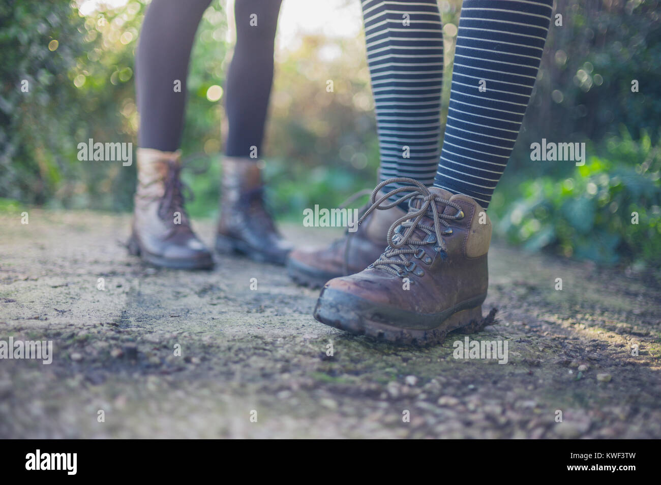 The shoes and feet of two young women standing outside in nature - Stock Image