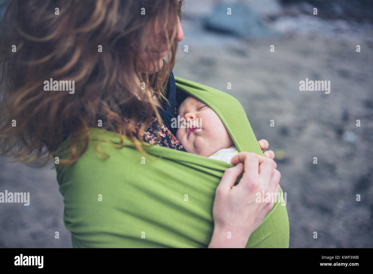 A young woman on the beach with her baby in a sling - Stock Image