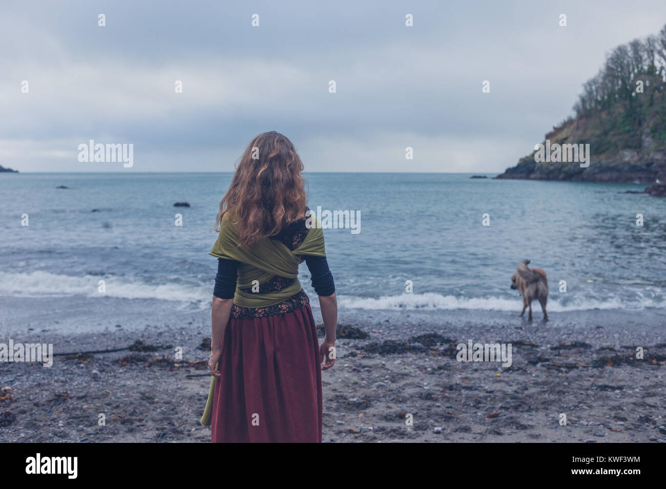 A young woman is walking her dog on the beach - Stock Image