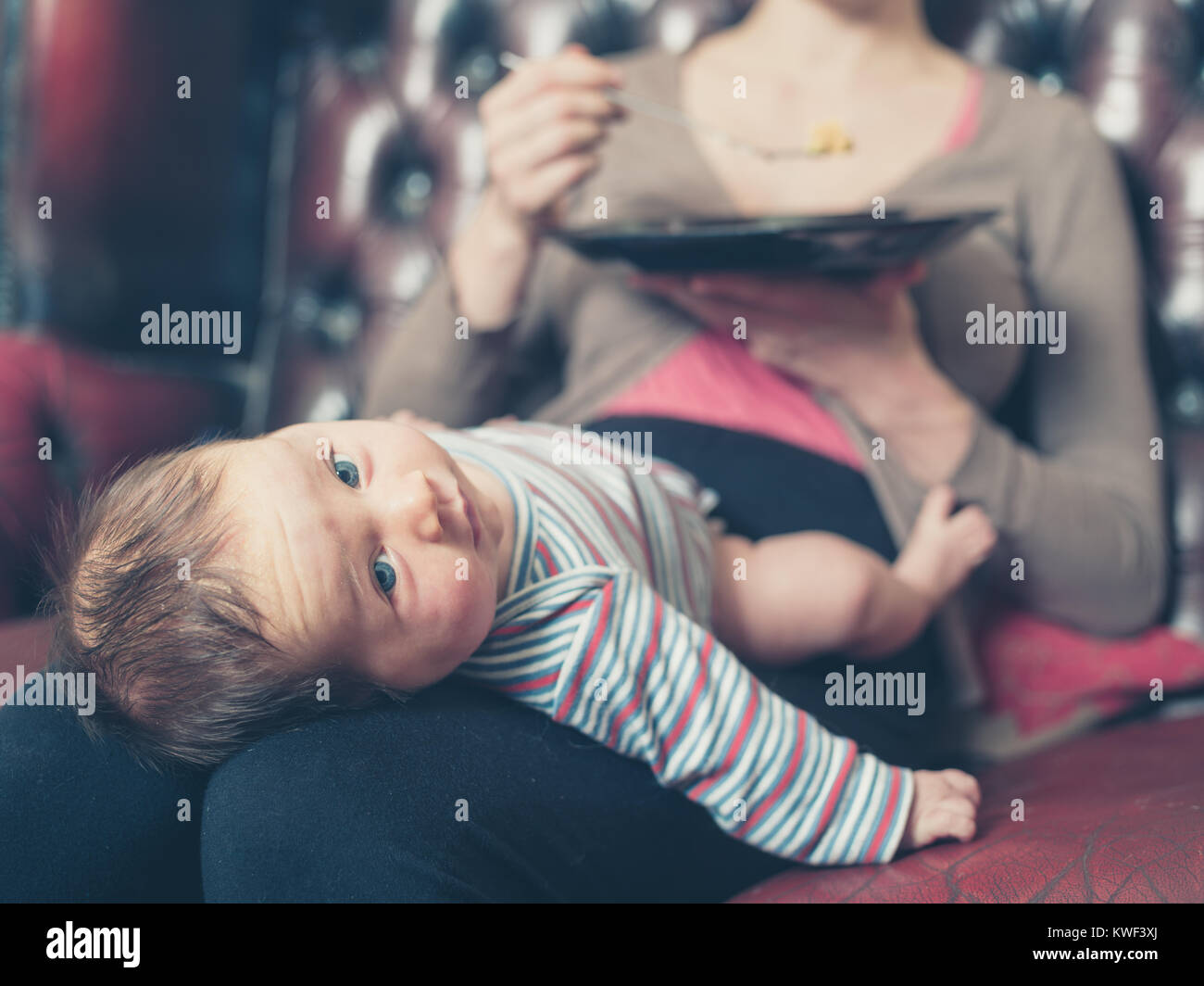 A young mother is sitting on a sofa and is trying to eat her dinner with her baby on her lap - Stock Image