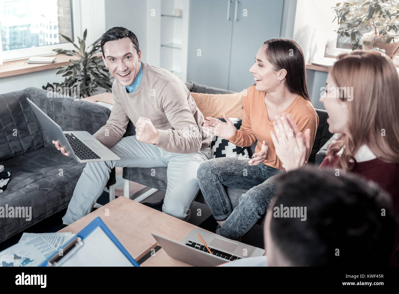 I succeeded. Joyful handsome satisfied man sitting in the office having fun with colleagues and holding the laptop. - Stock Image