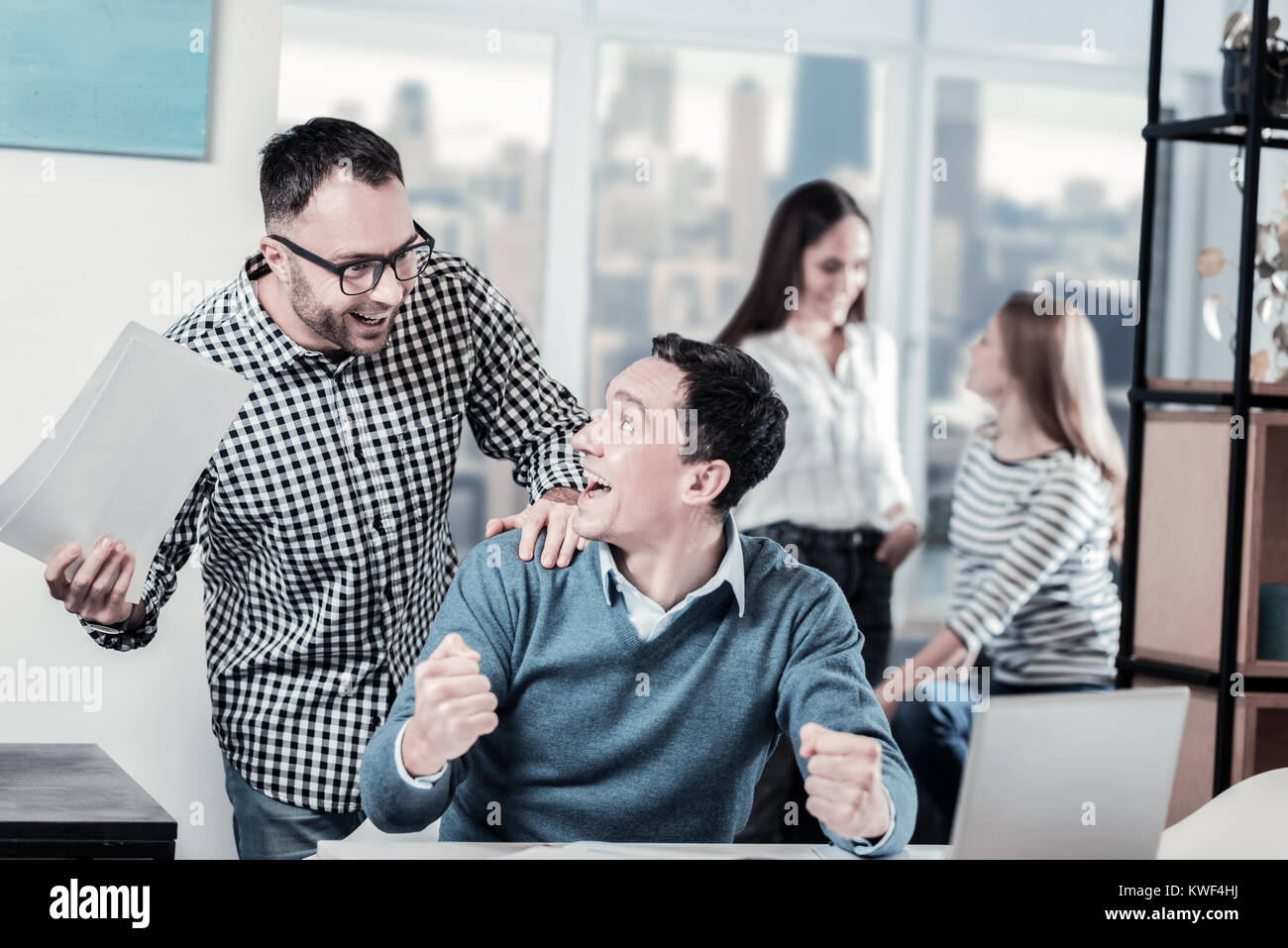 Incredibly situation. Friendly amazed nice-looking colleagues rejoicing together having fun and smiling. - Stock Image