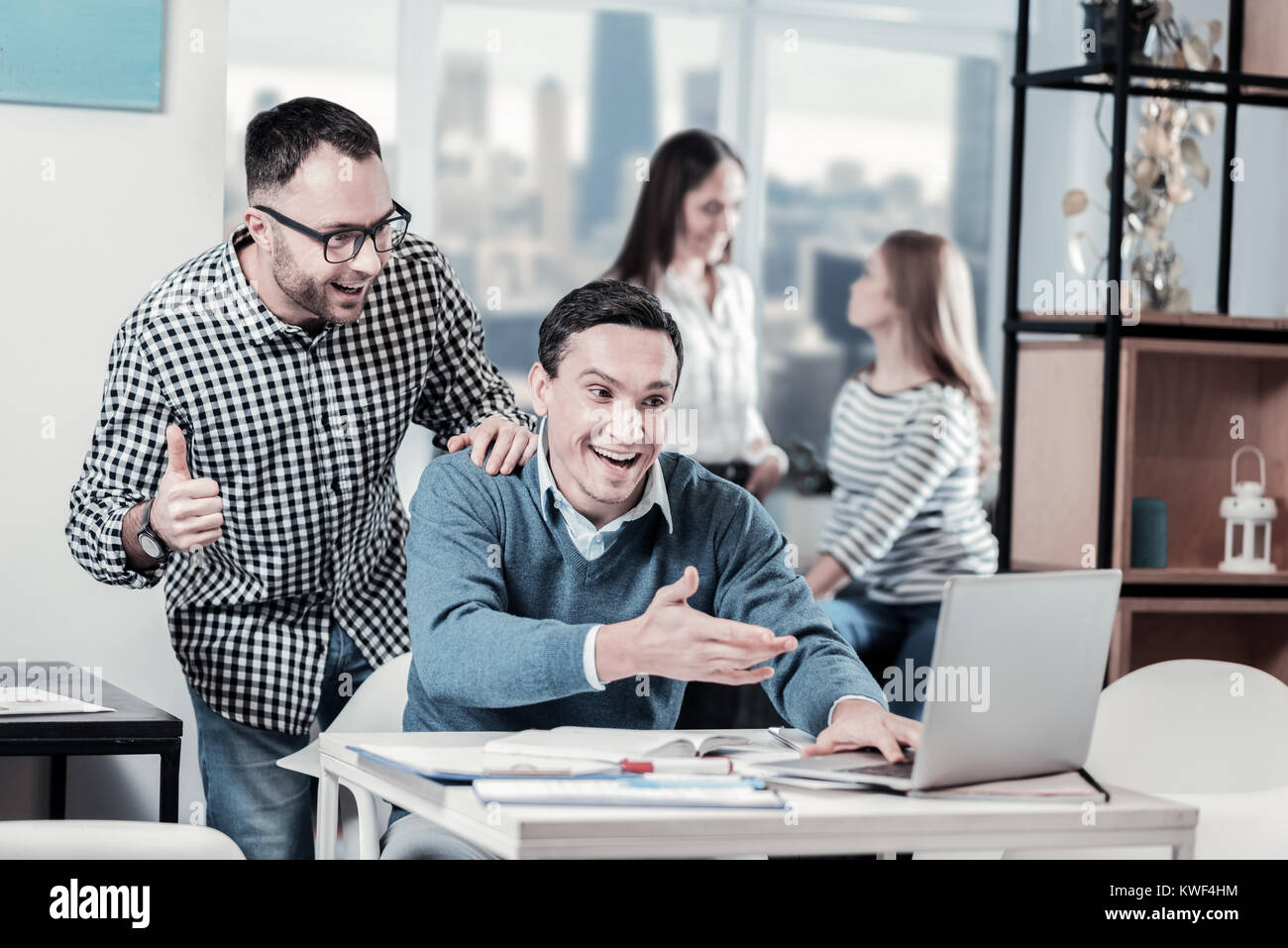 Do you believe. Funny satisfied amazed workers spending time together looking at the laptop and rejoicing. - Stock Image