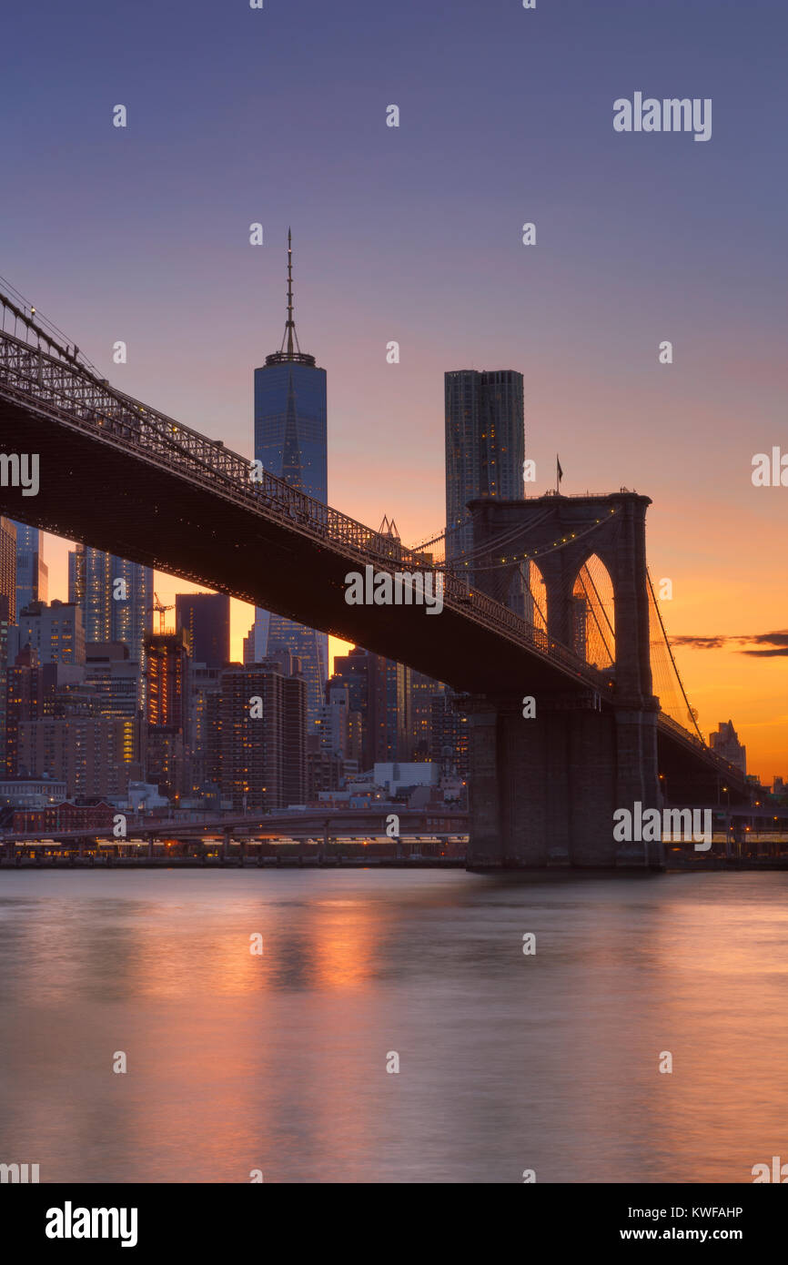 Brooklyn Bridge with the New York City skyline in the background, photographed at sunset. - Stock Image