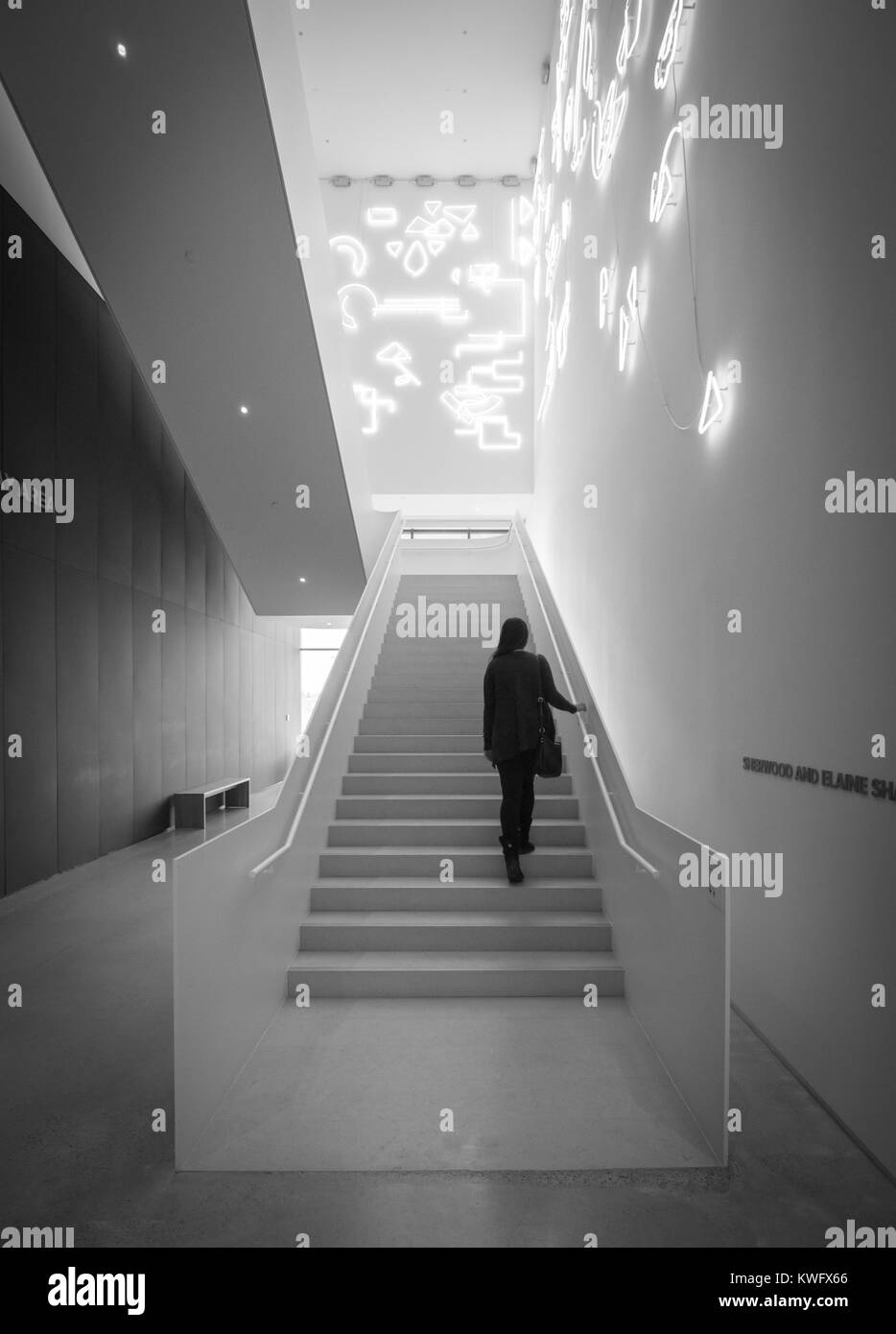 A young woman walks up stairs featuring a neon light installation named Lucky Charms by artist Pae White at the Stock Photo