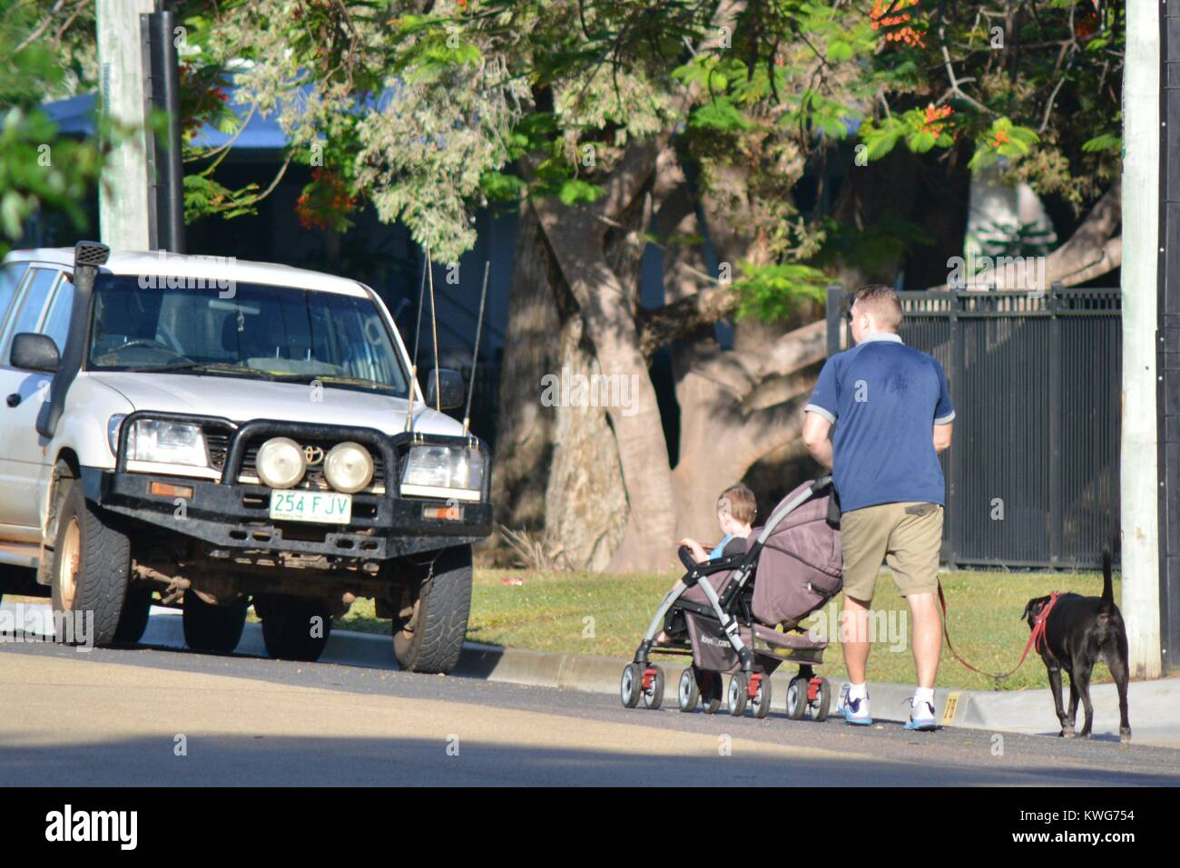Man walks with a pram and child and black dog along a suburban street, Townsville, Queensland, Australia - Stock Image