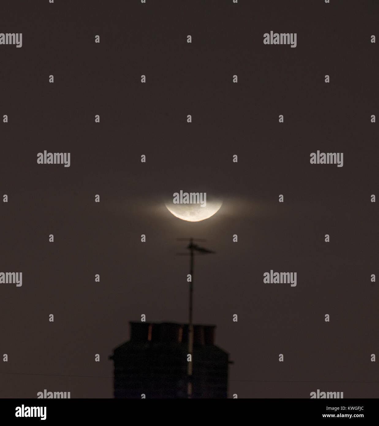 London, UK. 3 January 2018. 97% illuminated Waning Gibbous Moon rises through cloudy sky above London suburban rooftops, - Stock Image