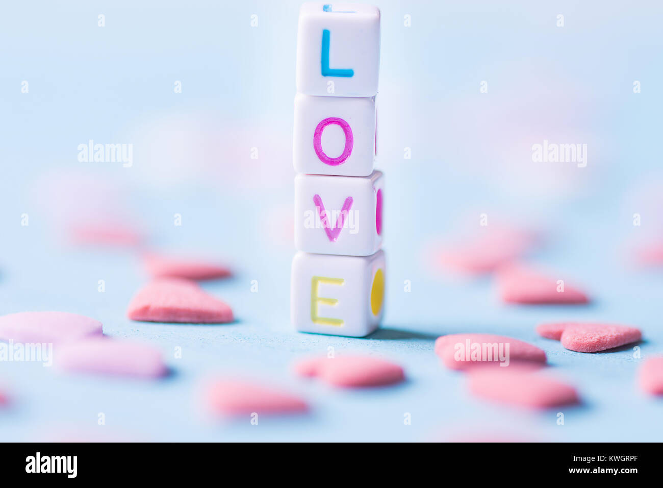 Word Love Constructed from Stacked Letter Cubes. Pink Sugar Candy Sprinkles Scattered on Light Blue Background. - Stock Image