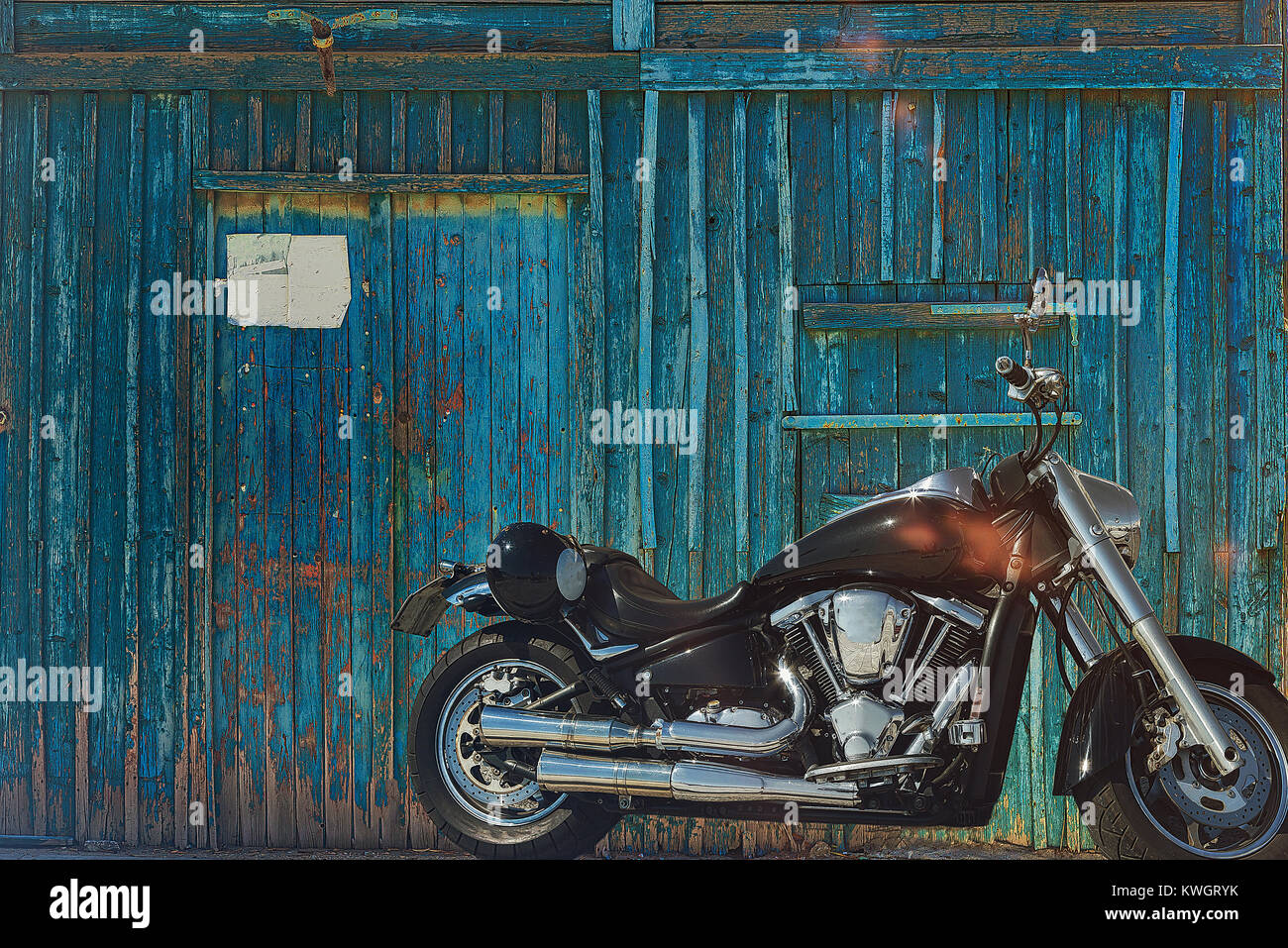 Motorcycle parked in a street on the island of Syros with a blue wooden wall as background. - Stock Image