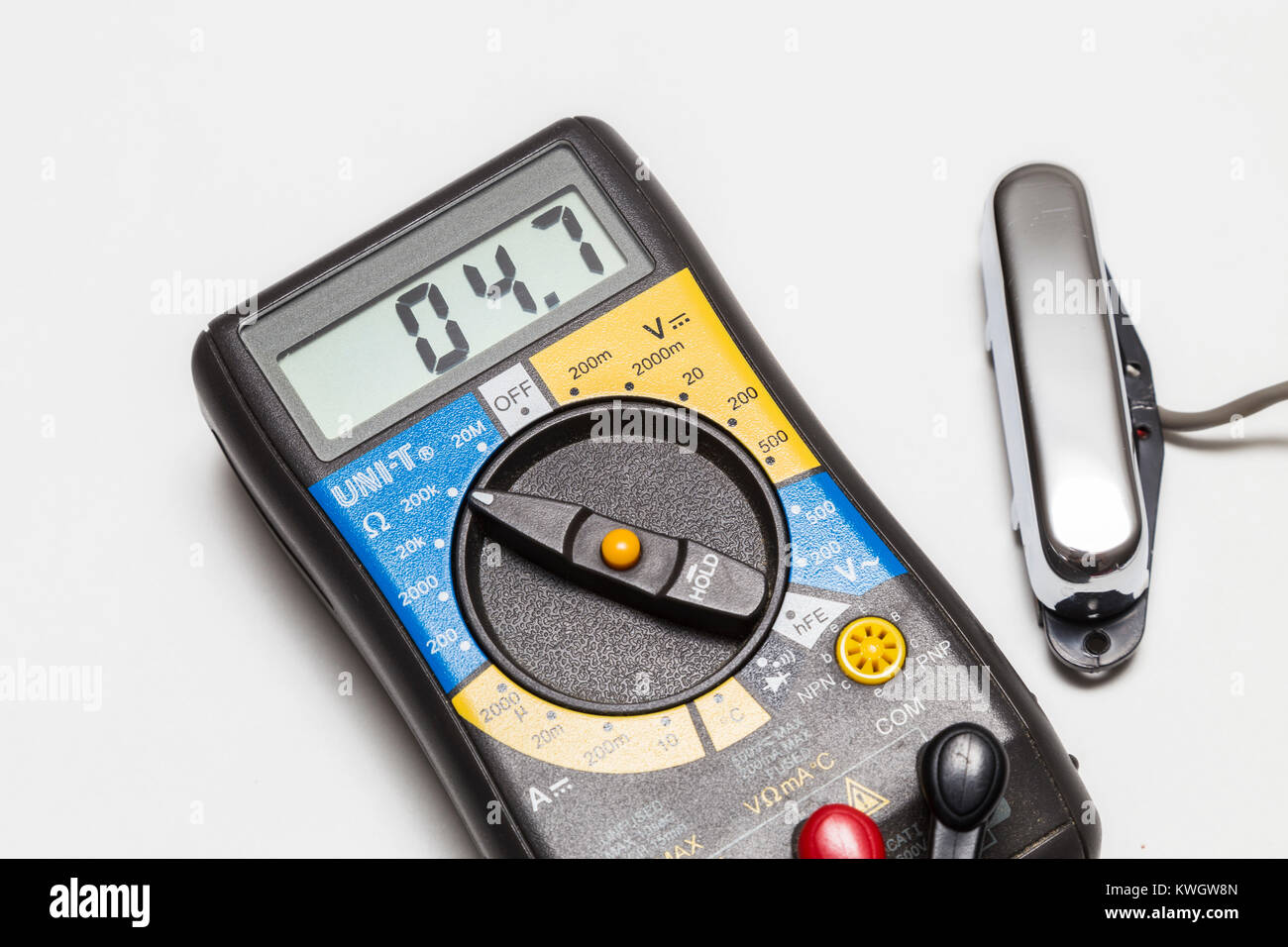 Testing the DC resistance on a telecaster type guitar neck 'lipstick' pickup using a multimeter. - Stock Image