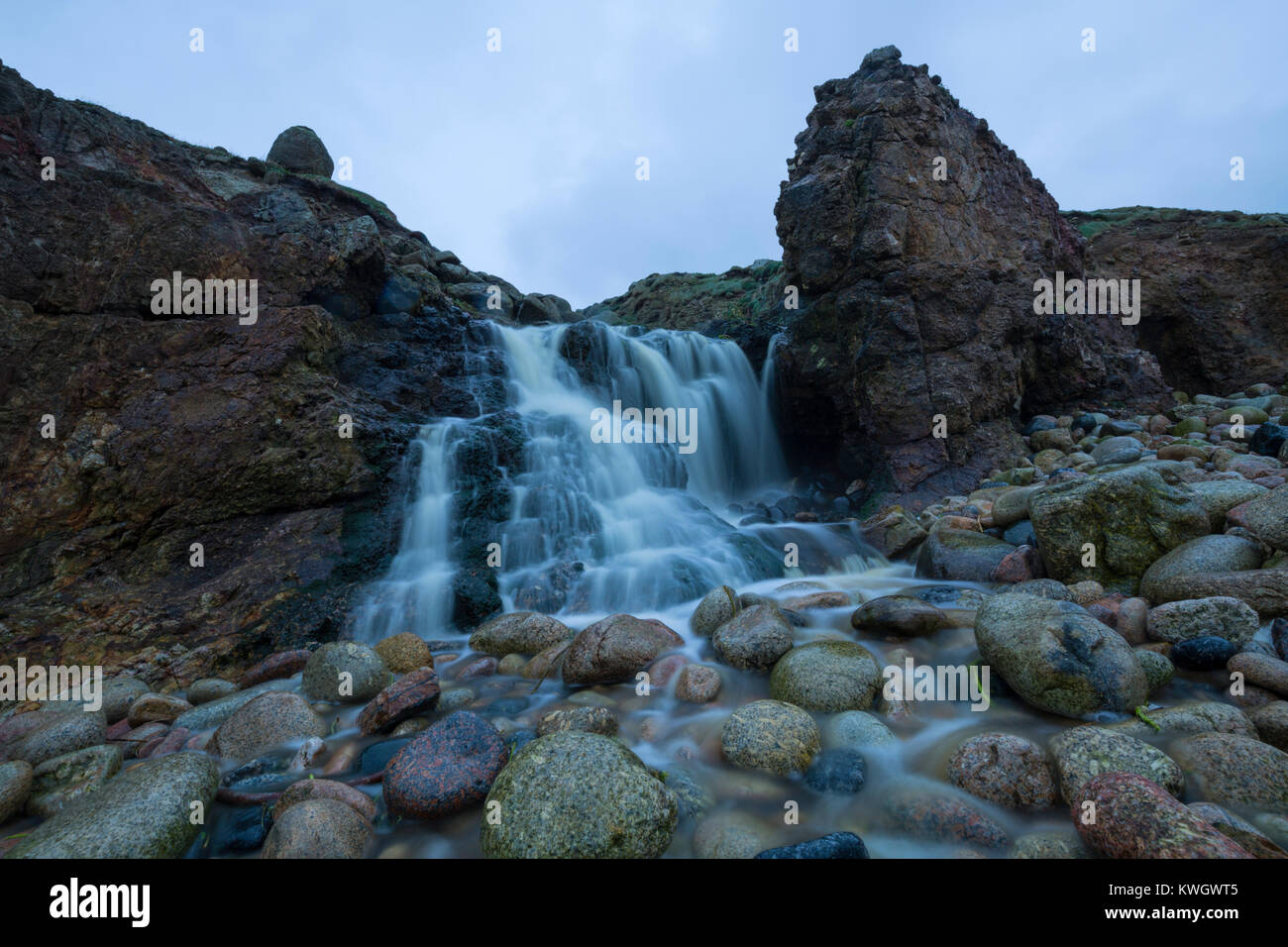 Waterfall onto the beach at Nanjizal Bay in West Cornwall Stock Photo