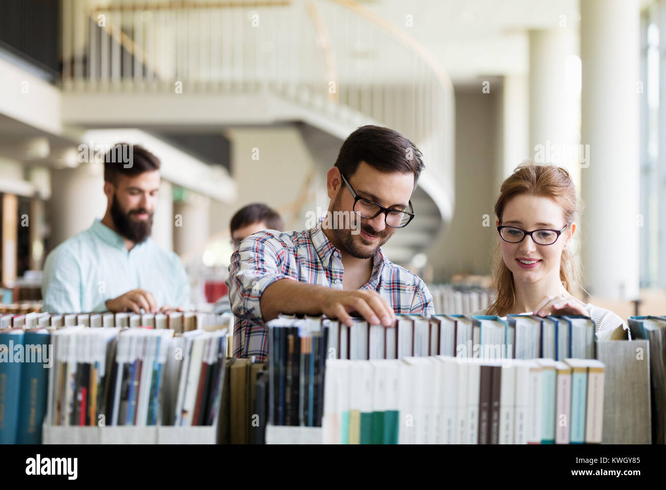 Happy young university students studying with books in library - Stock Image