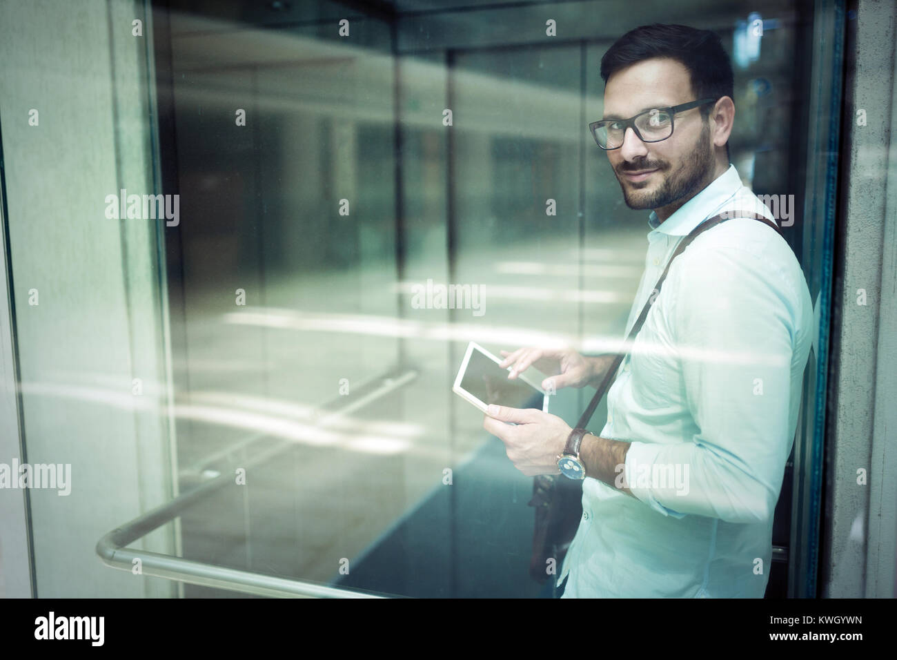 Handsome young businessman using his digital tablet - Stock Image