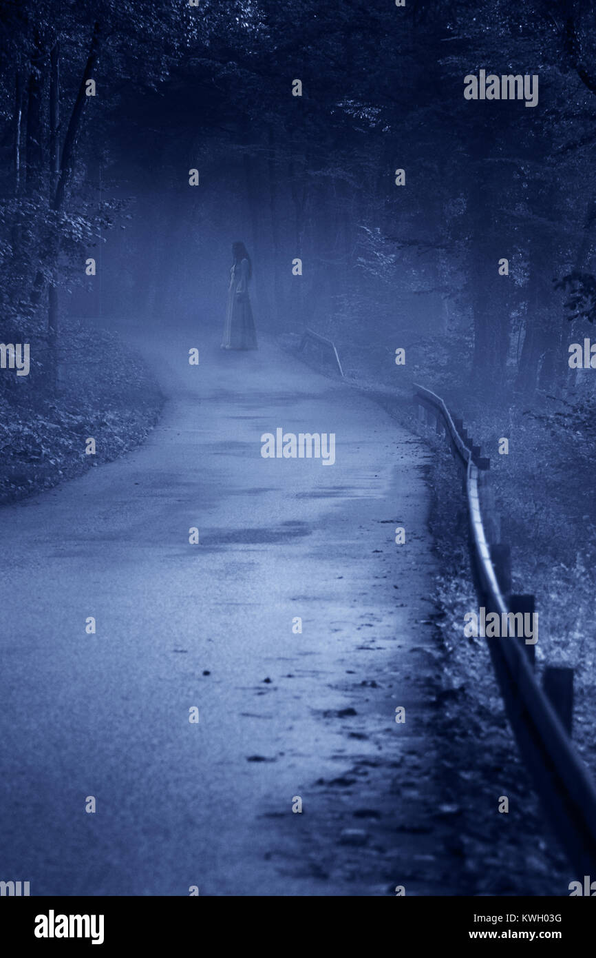 Mysterious Woman Ghost in White Dress in the Misty Forest Road, vintage noise filter - Stock Image