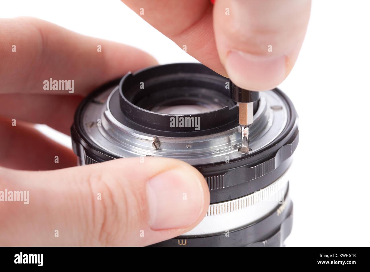 Technician repairing lens, removing lens mount - Stock Image