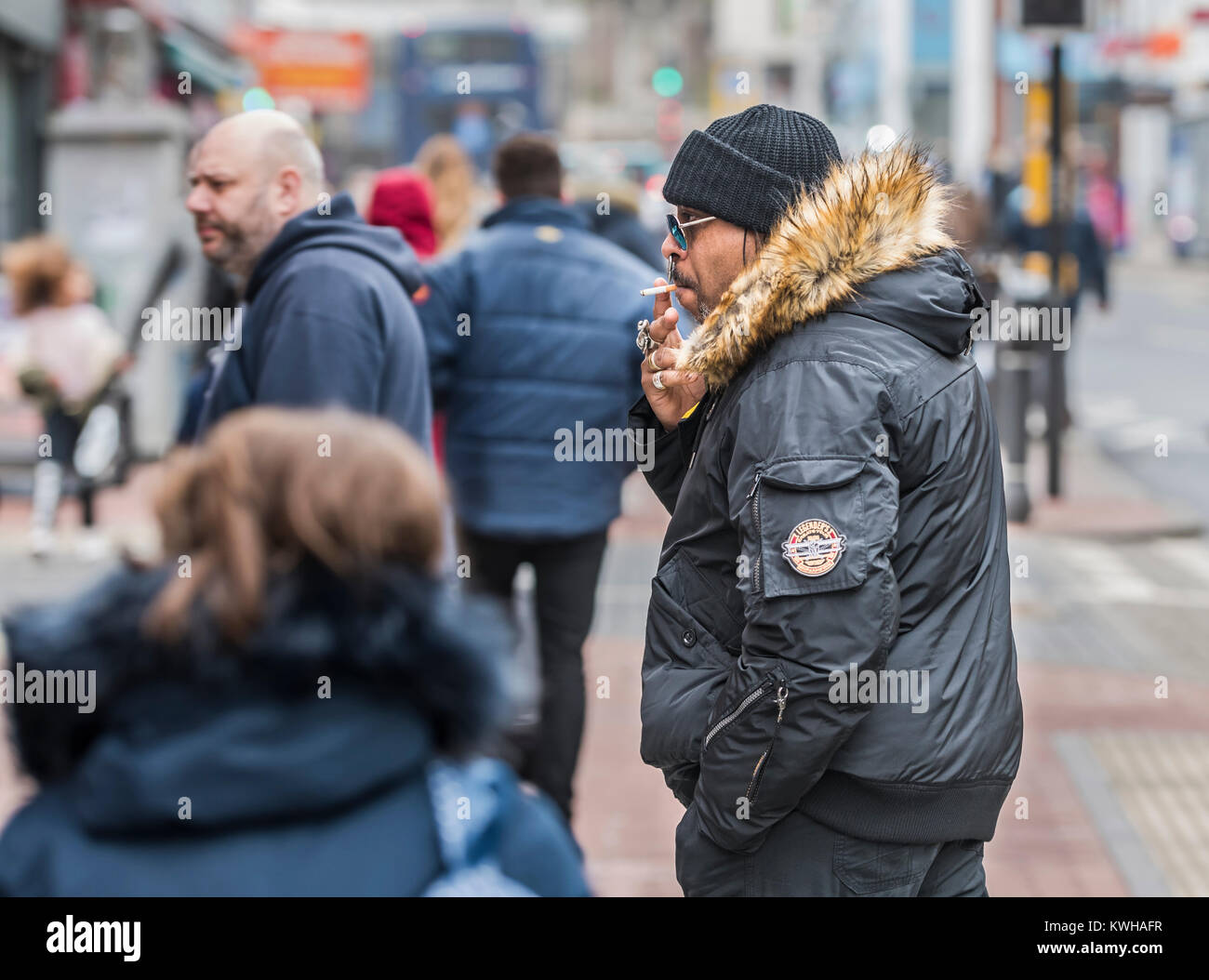 Black man dressed in Winter clothes smoking a cigarette in Winter in England, UK. - Stock Image