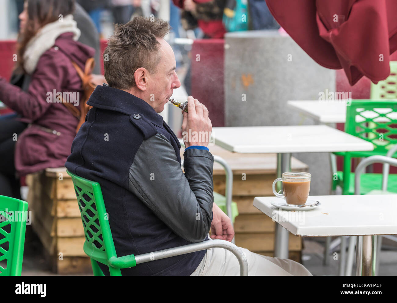 Man sitting at a cafe outside in Winter vaping on an Electronic cigarette in England, UK. - Stock Image