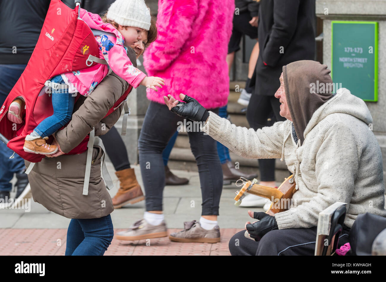 Young child on woman's shoulders giving money to a street busker in the UK. Handout - Stock Image