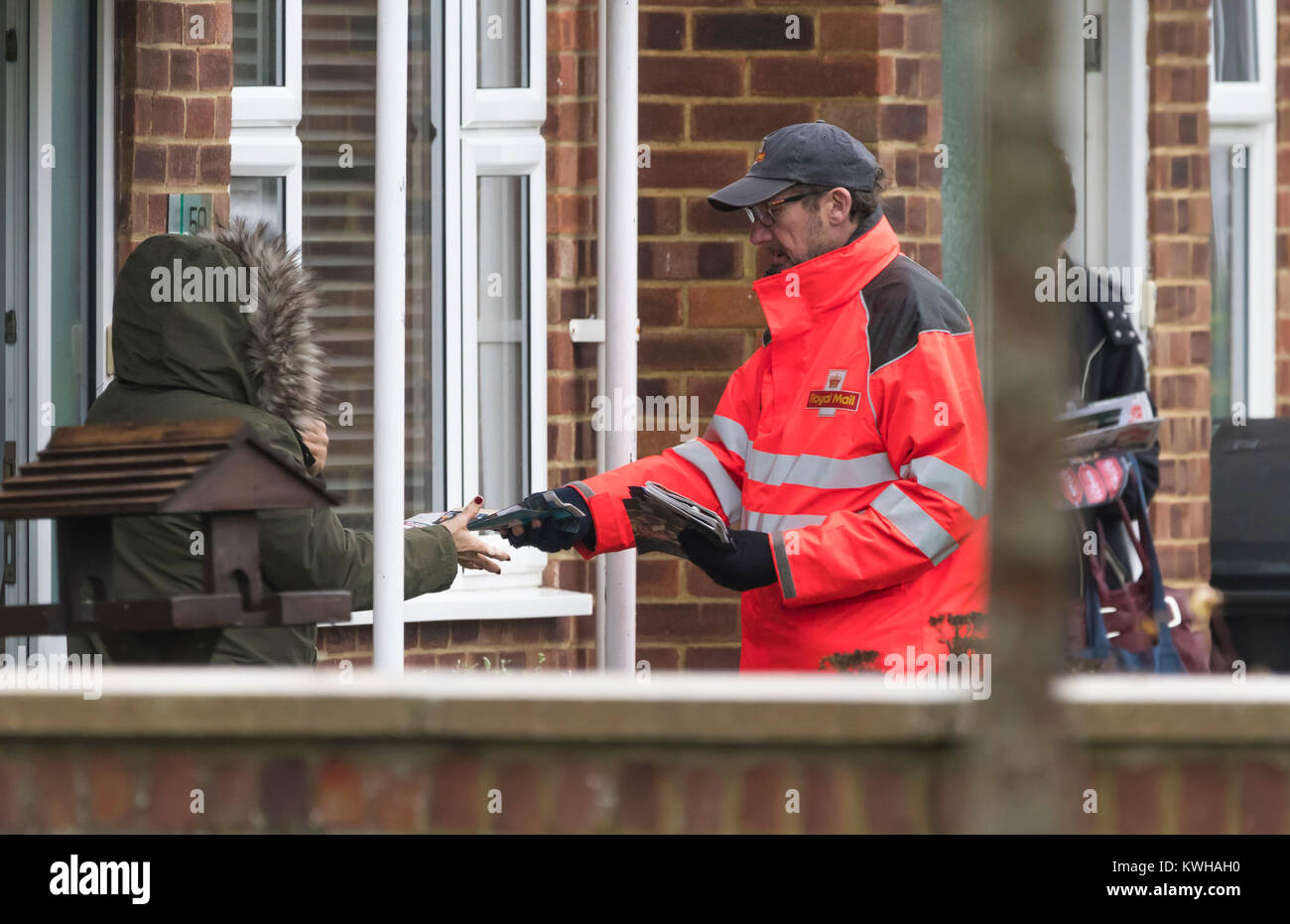 Royal Mail postman passing post to someone in England, UK. - Stock Image