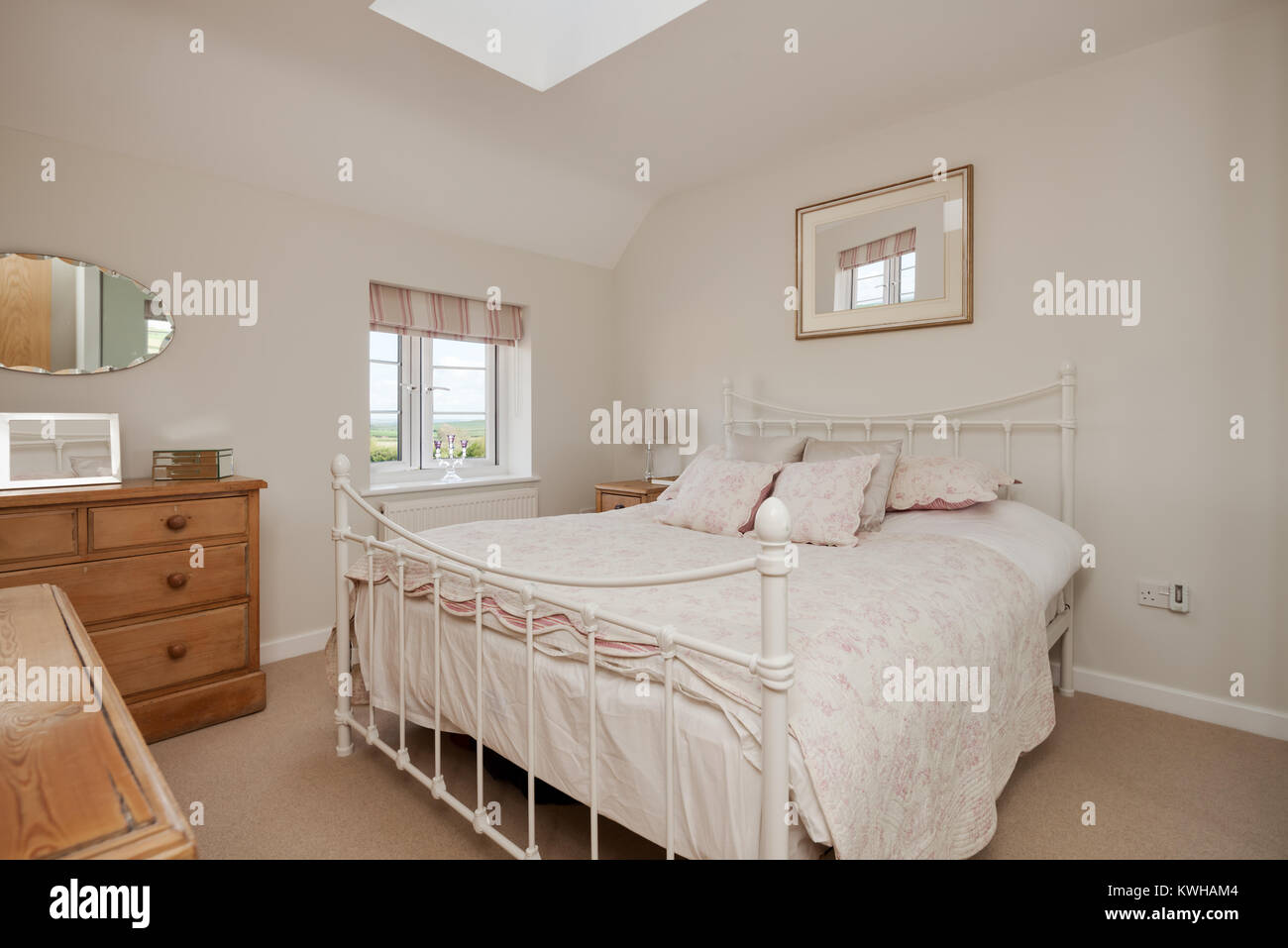 Traditional cottage style bedroom modestly dressed with floral pattern bedspread, painted wrought iron style bedstead, - Stock Image