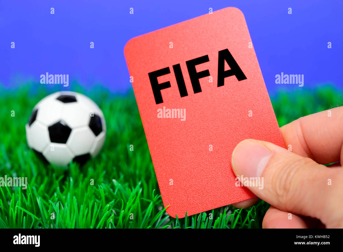 Miniature football and hand with red map, Fifa scandal, Miniaturfußball und Hand mit roter Karte, Fifa-Skandal - Stock Image