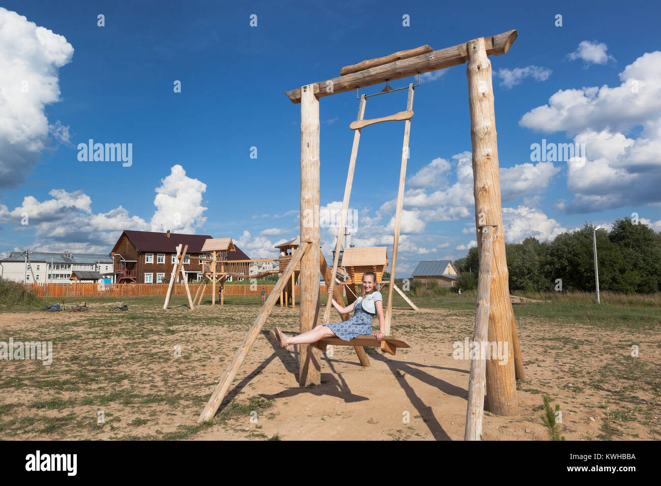 Girl swinging on a huge wooden swings at the park - Stock Image