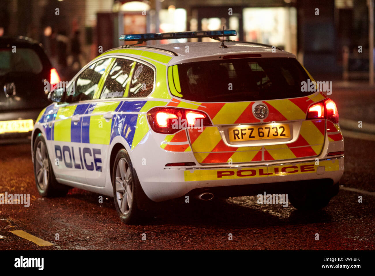 police vehicle following car at night in city centre belfast northern ireland uk Stock Photo