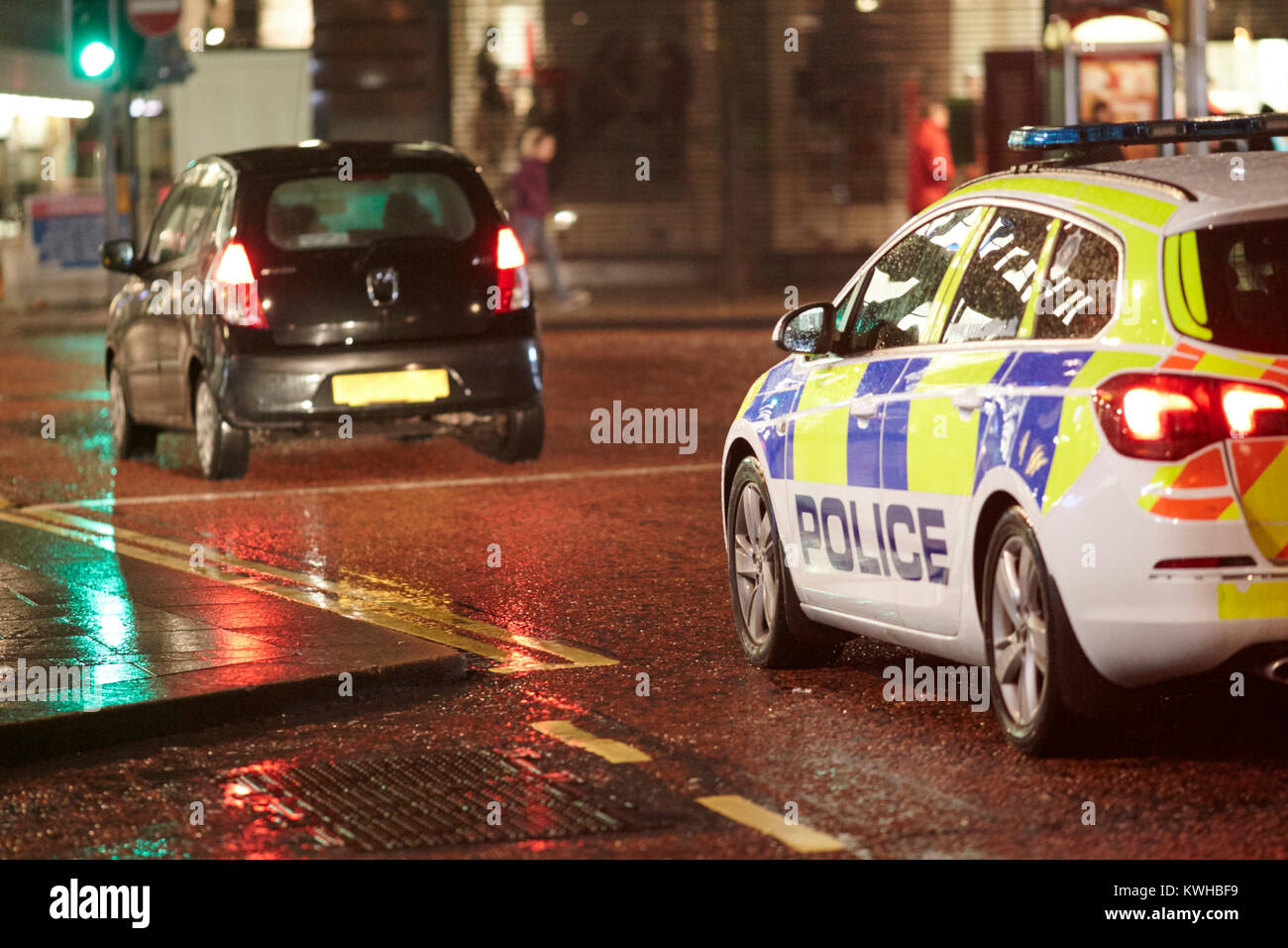 8f1f02d68e police vehicle following car at night in city centre belfast northern  ireland uk - Stock Image