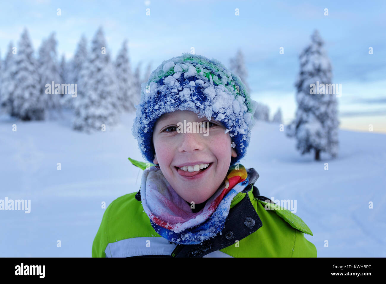 Portrait of a smiling young boy with his face and beanie covered with snow after winter playing on a mountain with - Stock Image