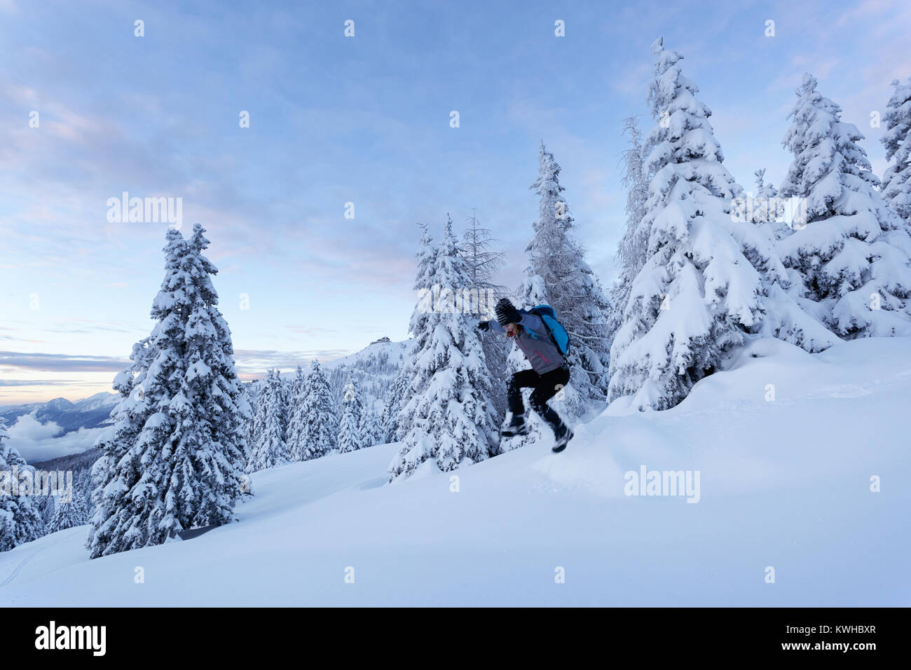 Woman hiker in active outfit, jumping in deep snow between frozen spruces on the mountain, Krvavec, Slovenia. - Stock Image