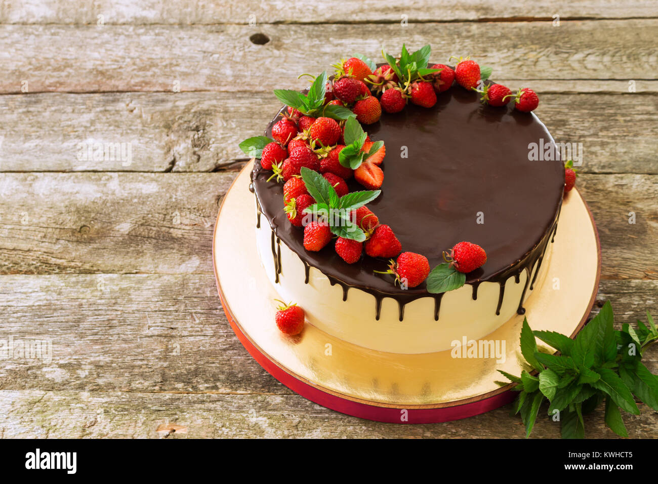 Beautiful festive cake covered with melted chocolate with strawberries and mint leaves - Stock Image