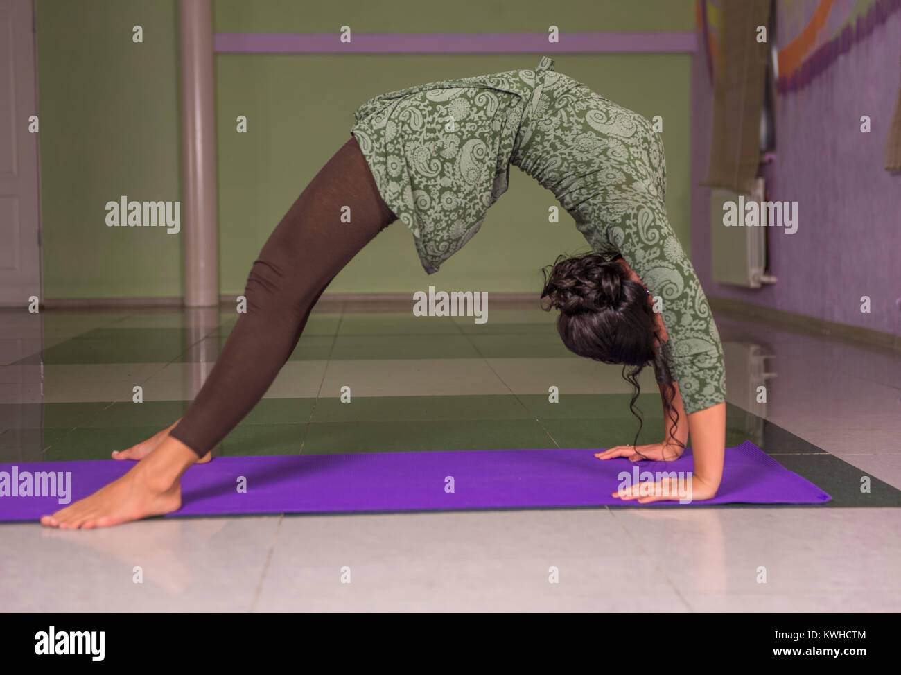 Yoga woman practices yoga lesson in a studio - Stock Image